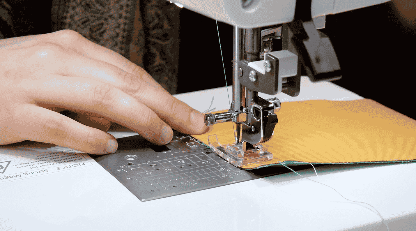 A picture containing text, sewing machine, indoor, person  Description automatically generated